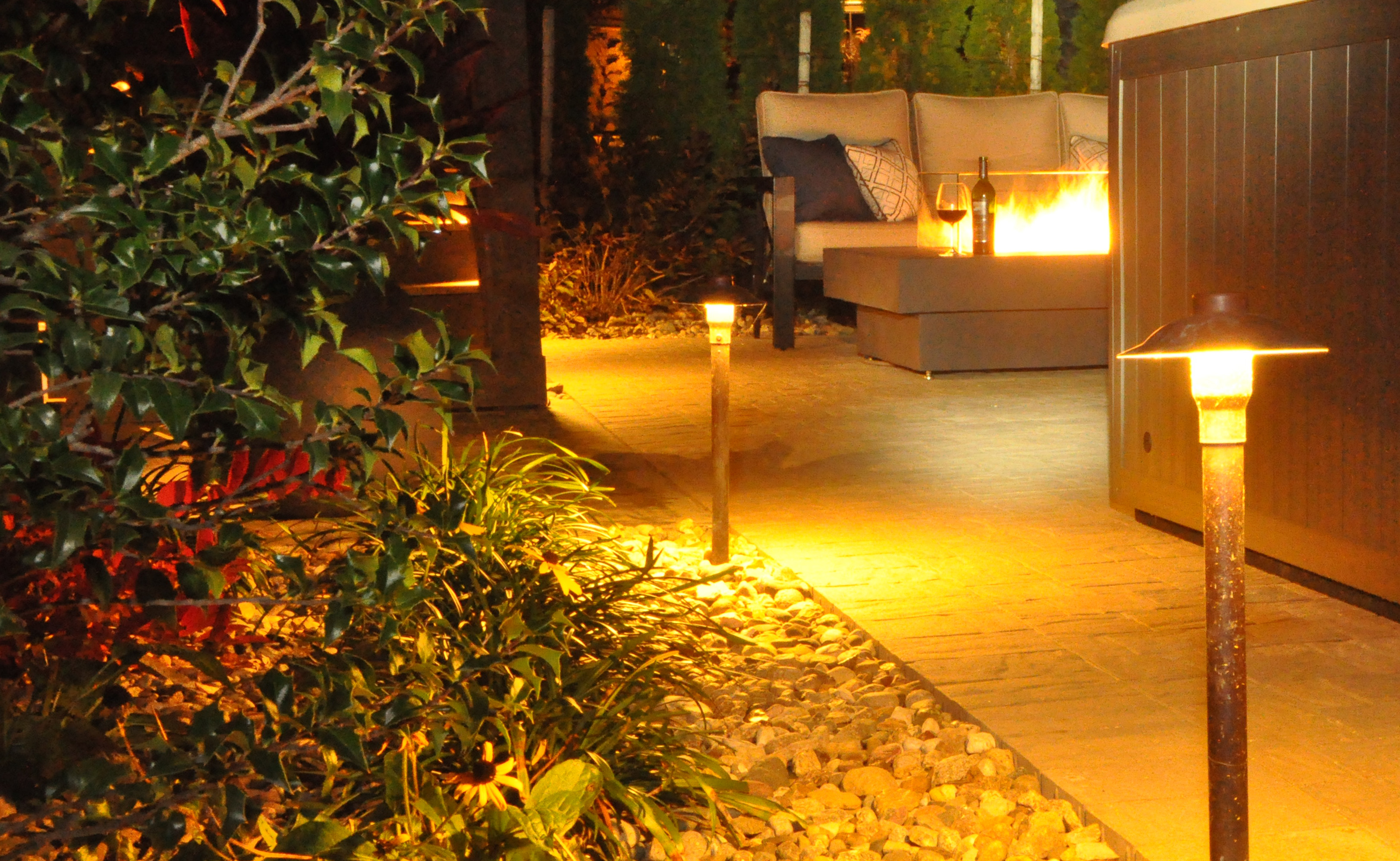 Professionally designed fire pits and lighting add elegance to the landscape.