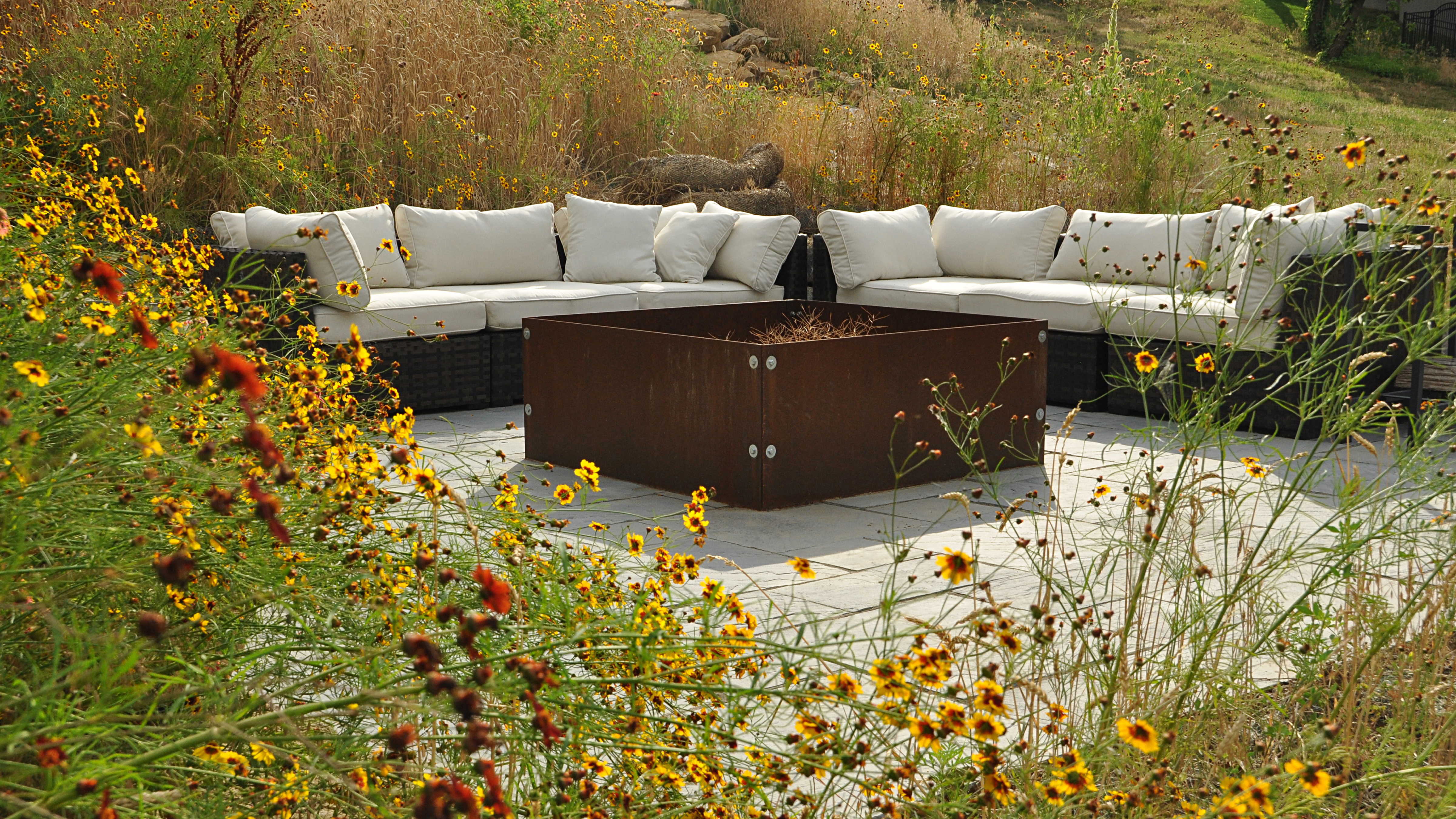 The finished hillside retreat is a relaxing oasis in the midst of native beauty. The rusty corten steel fire pit, although contemporary in design, is in perfect harmony with its surroundings.