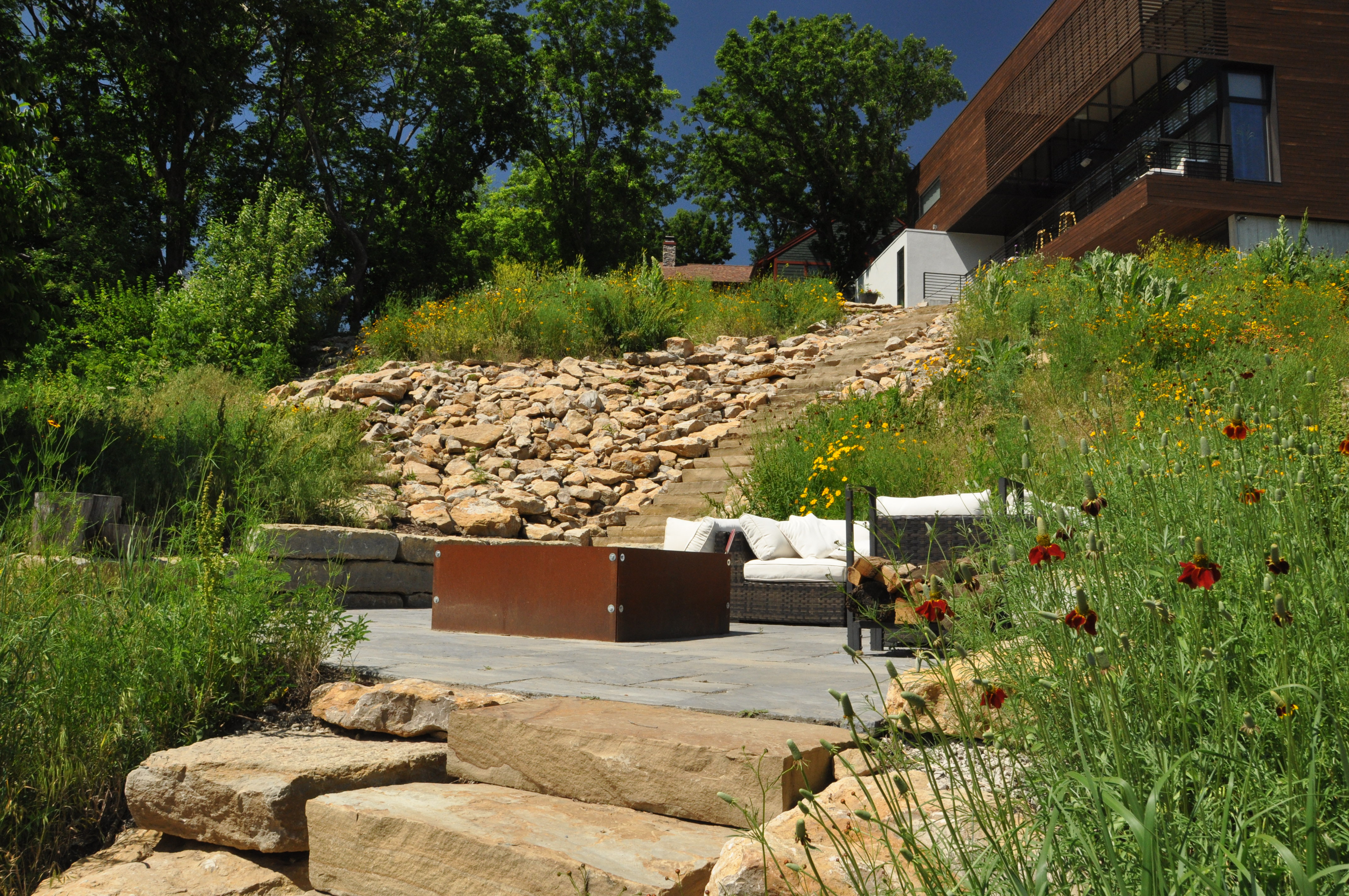This contemporary lakeside home was built atop a hill overlooking a large lake. During construction, excavators left tons of limestone rock on the crest of the hill. Rather than face the expense of removing it from the site, Embassy designer Dan Nelson found a way to utilize it in the design. The stone was used to cover the slope and a native prairie mix was sown on the poor soil on the hillside.