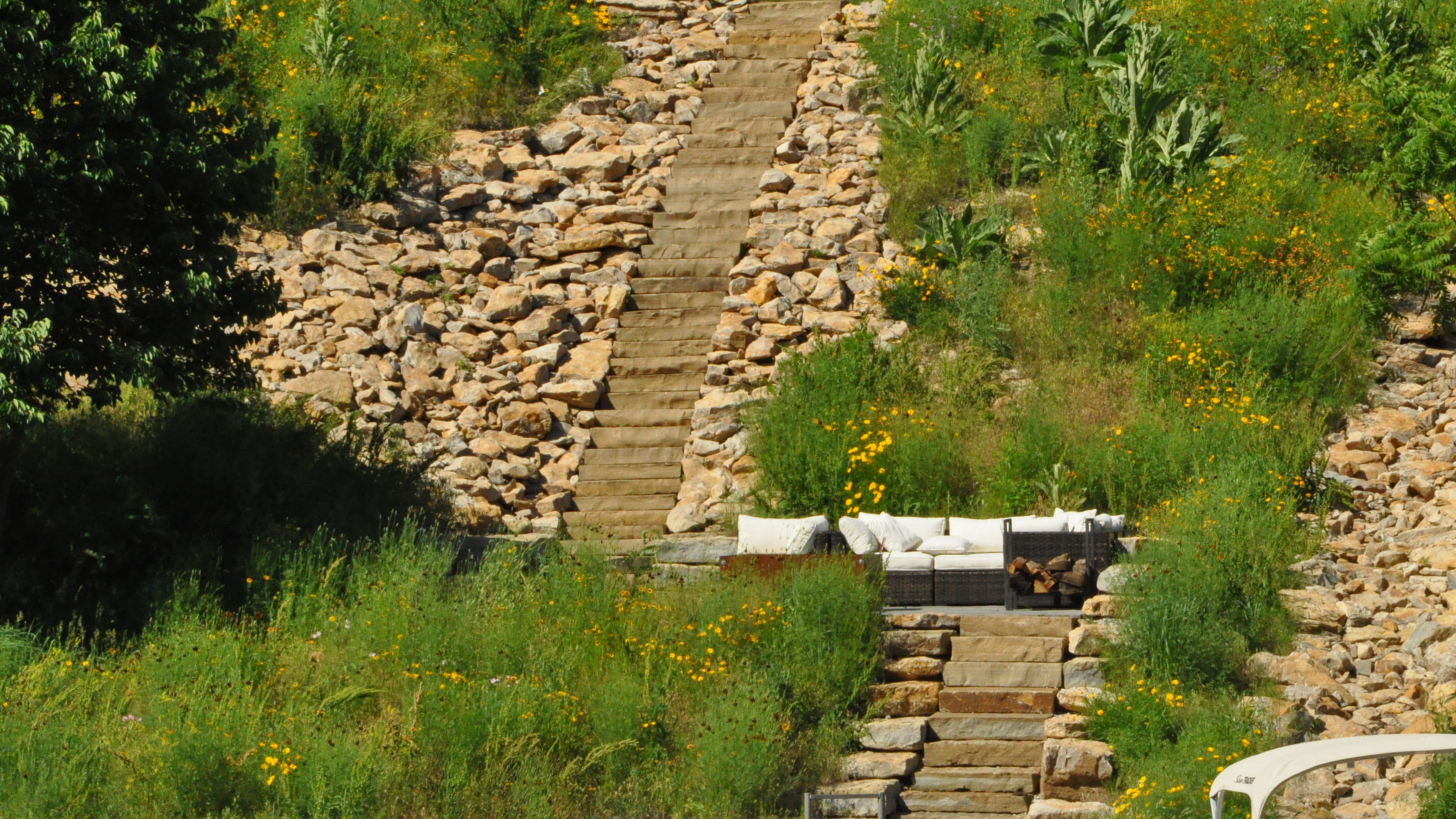Native plants thrive on the hot, sunny hillside with minimal maintenance. As a further benefit, the stone provides a pathway for rooftop water flow to reach the lake without creating erosion issues or lake contamination. Since natives rarely need chemical applications, there is little chance of water pollution from run-off.