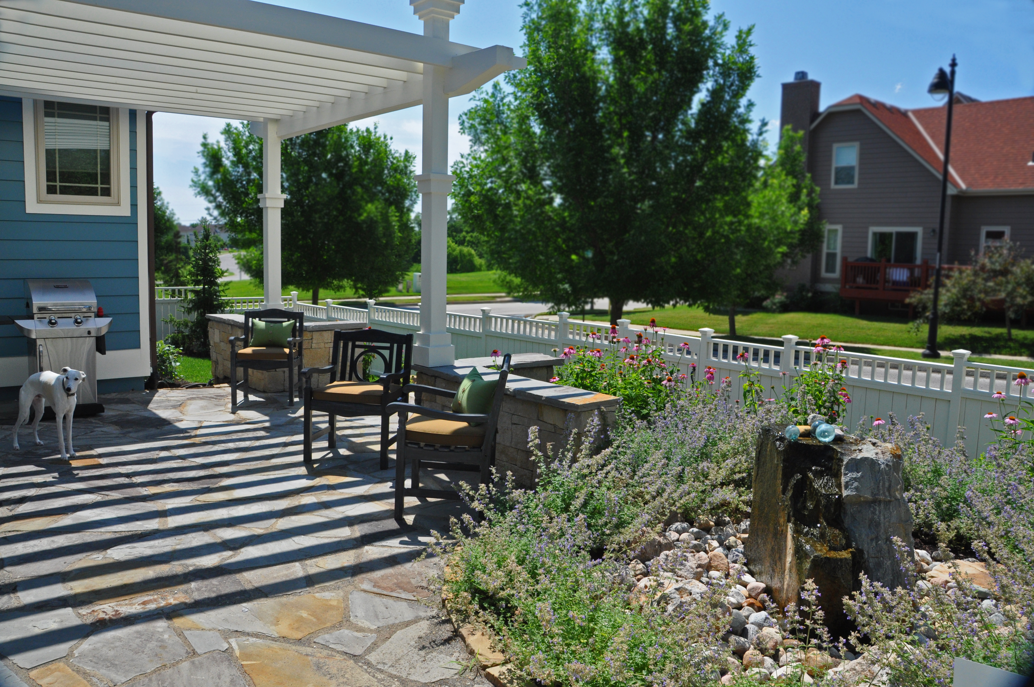 The shaded stone patio looks out onto a colorful, but low maintenance garden.