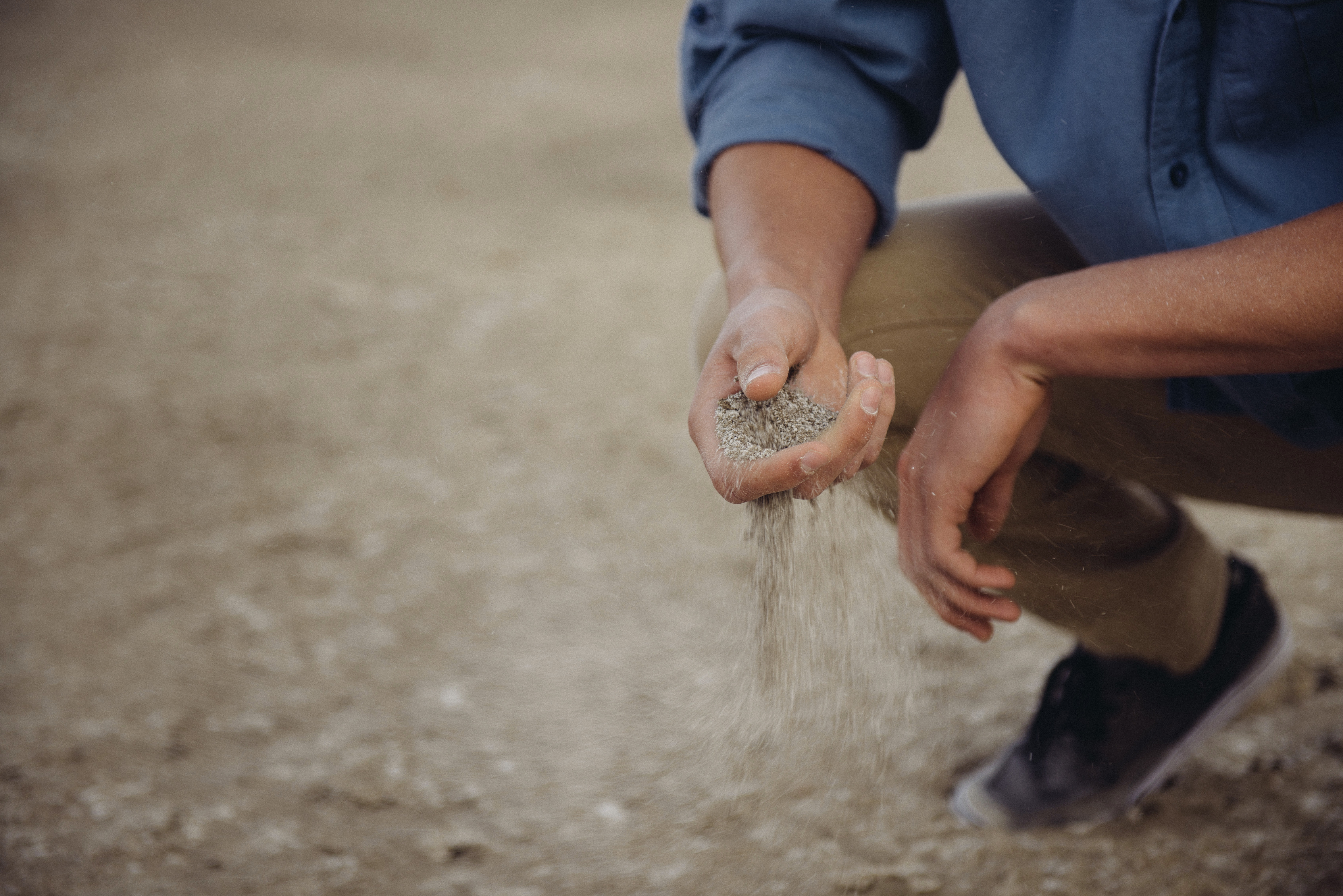 Dry sandy soil runs quickly and easily through your hands.